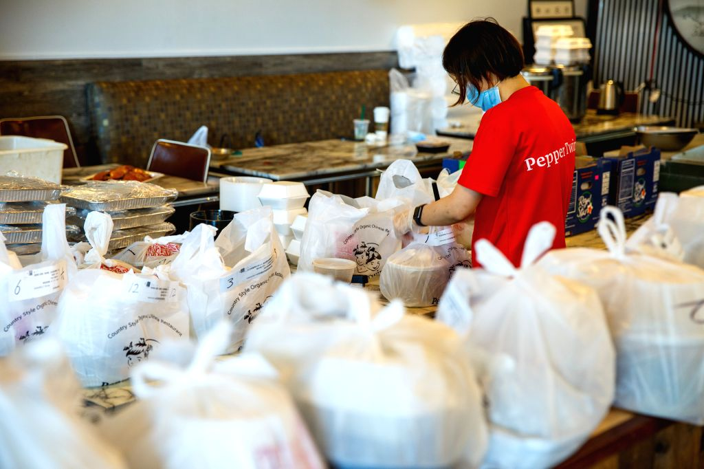 A staff member wearing a face mask packs meals at a Chinese restaurant in Houston, Texas, the United States, on July 2, 2020. U.S. state of Texas added more than ...