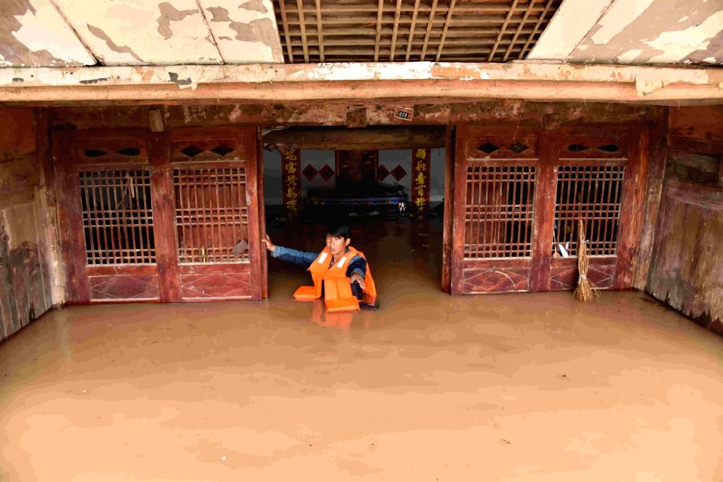 A street officer helps in searching for people trapped by flood in Songtao Miao Autonomous County of Tongren City, southwest China's Guizhou Province, June 23, 2017. Flash floods broke out ...