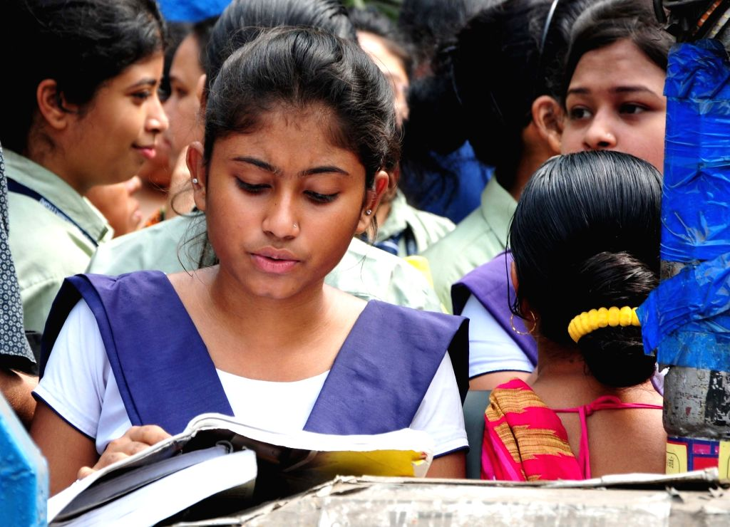 A student appearing for her class 12th Board examination, busy in last-minute revision outside their exam center in Kolkata on March 27, 2018.