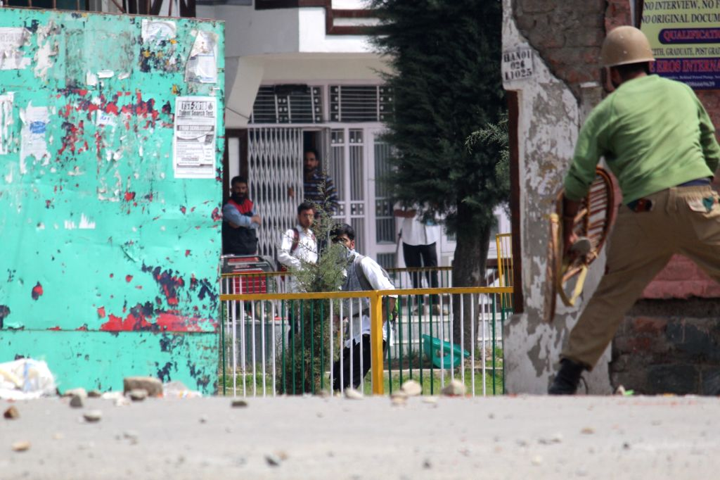 A student pelts stones at a security personnel as students of Handwara's Government Degree College clashed withsecurity forces over civilian killings in south Kashmir; in Jammu and Kashmir's ...
