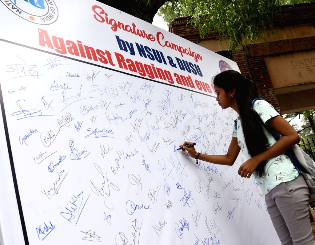 A student signs a board set up as part of a Signature Campaign initiated by NSUI and DUSU against ragging and eve-teasing, in New Delhi on July 25, 2019.