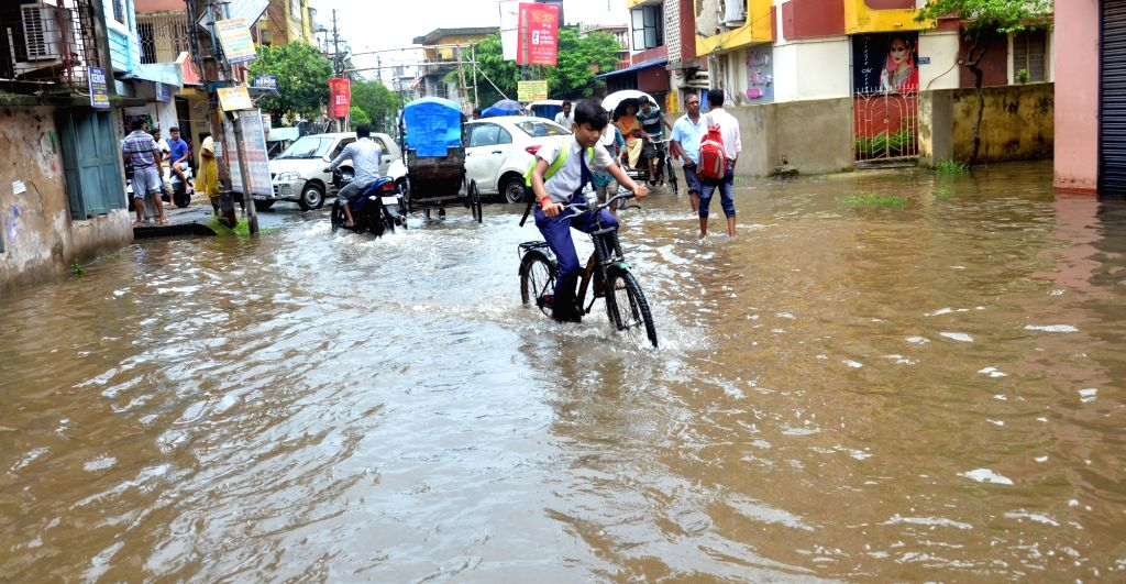 A student struggles through a waterlogged street after heavy rains lashed Kolkata, on July 23, 2018.