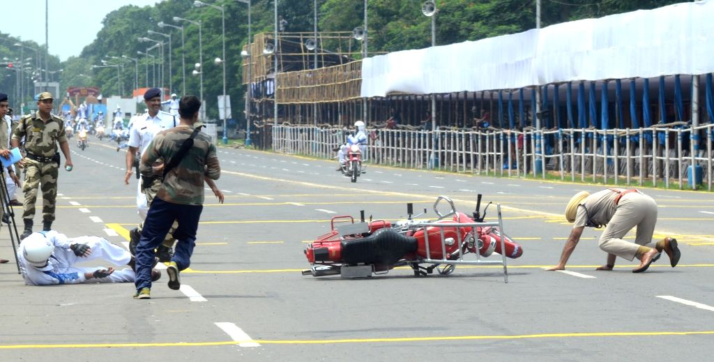 A stunt rider from the motorcycle display team of Indian Military's Army Service Corps 'Tornadoes' skids off the bike during rehearsals ahead of Independence Day celebrations, in Kolkata on ...