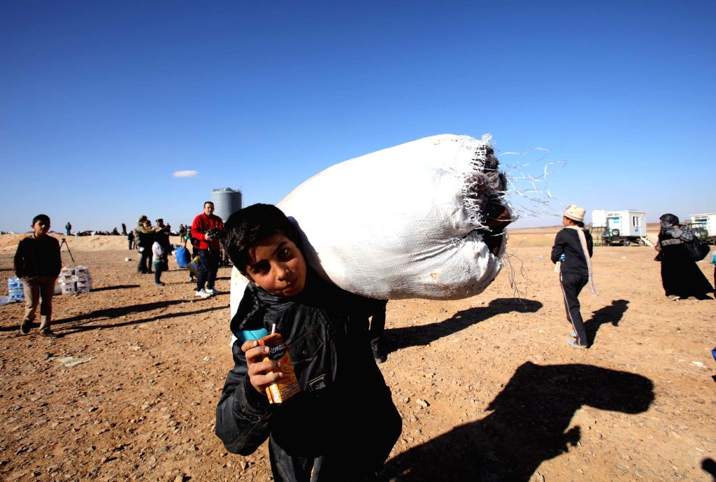 A Syrian refugee boy carrys his luggages after his family entered Jordanian territory, near the town of Ruwaished, at the Hadalat area, east of Amman, Jordan, Jan. ...