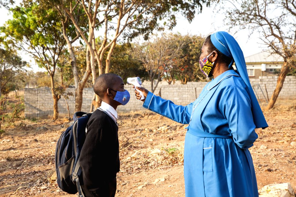 A teacher checks the temperature of a student at Mejocama Primary and Secondary School in Lusaka, Zambia, Sept. 21, 2020. Zambia National Education Coalition ...