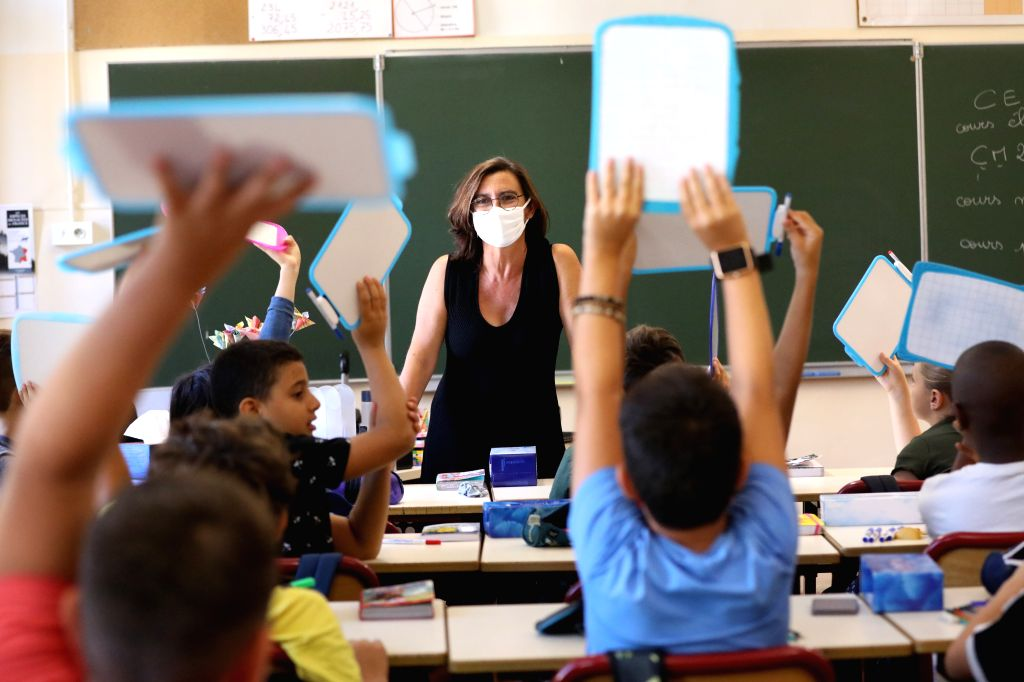 A teacher wearing a protective mask teaches in her classroom on the first day of the new school year in Nice, southern France, Sept. 1, 2020. The new school year ...