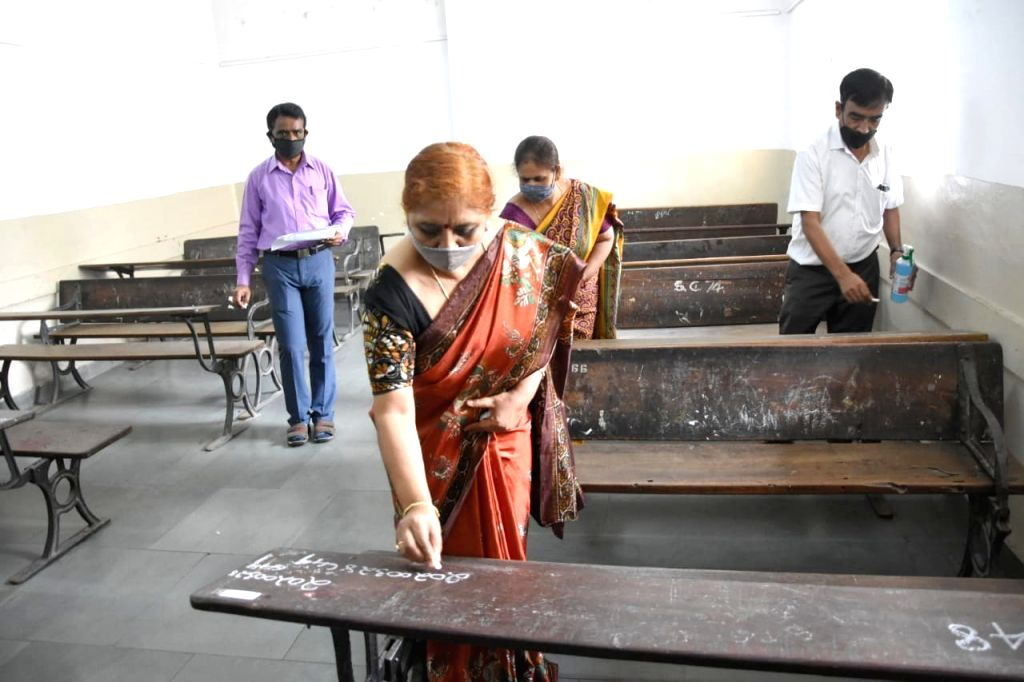 A teacher writes seating arrangements on the desks at Seshadripuram School ahead of conducting the remaining Secondary School Leaving Certificate (SSLC) exams, amid Unlock 1.0 or phased ...
