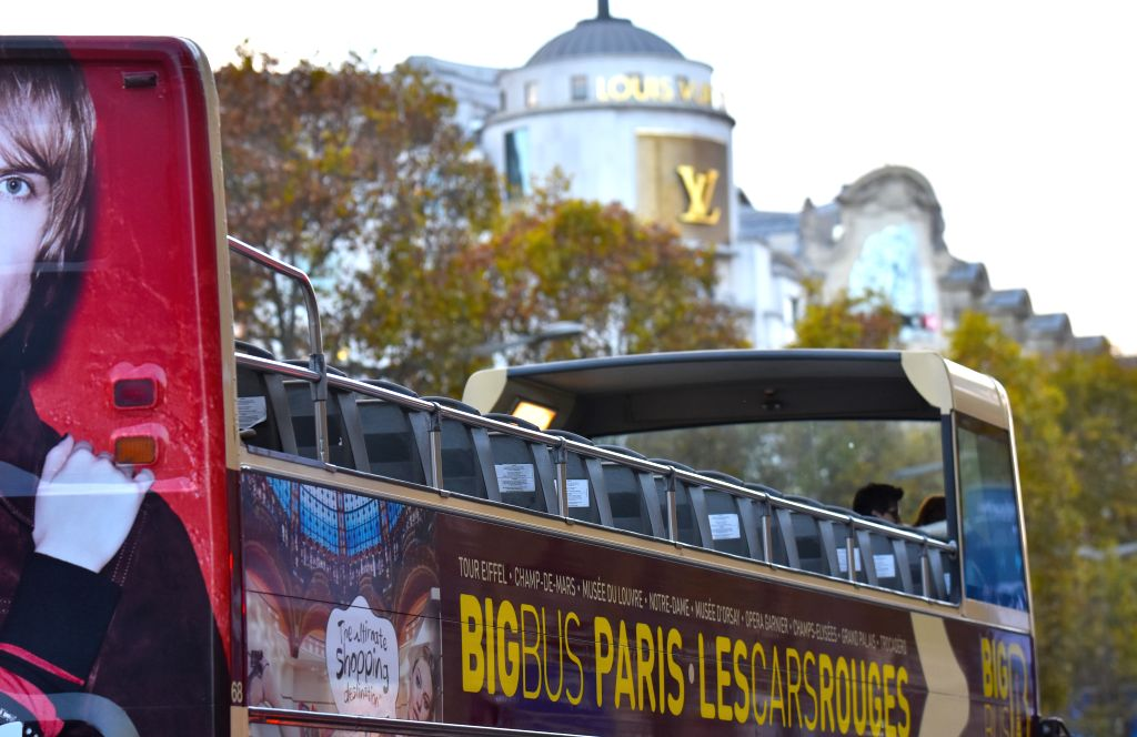 A tour bus with few passengers drives along the Champs-Elysees Avenue in Paris, capital of France, on Nov. 18, 2015. A large number of foreign tourists cancelled or ...