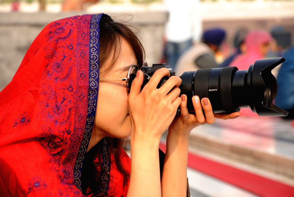 A tourist clicks pictures at the Golden Temple during the 550th birth anniversary celebrations of Guru Nanak Dev in Amritsar on Nov 12, 2019. - Nanak Dev