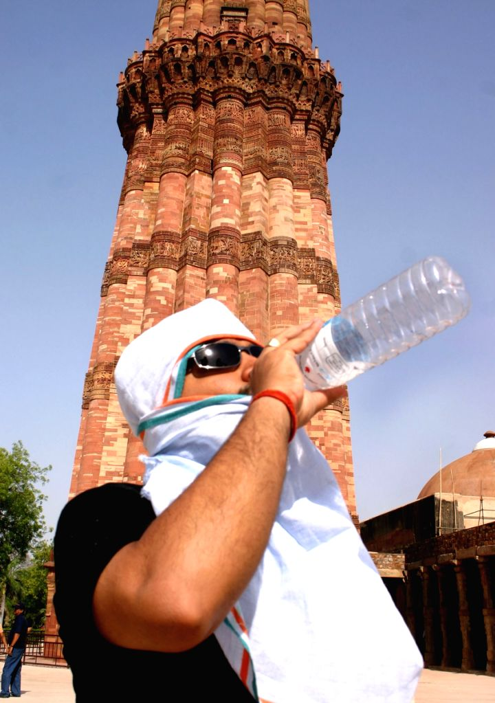 A tourist quenches his thirst at Qutab Minar as mercury level rises in New Delhi on Friday. The hot winds blowing form Rajasthan have increased day temperatures across northern India.