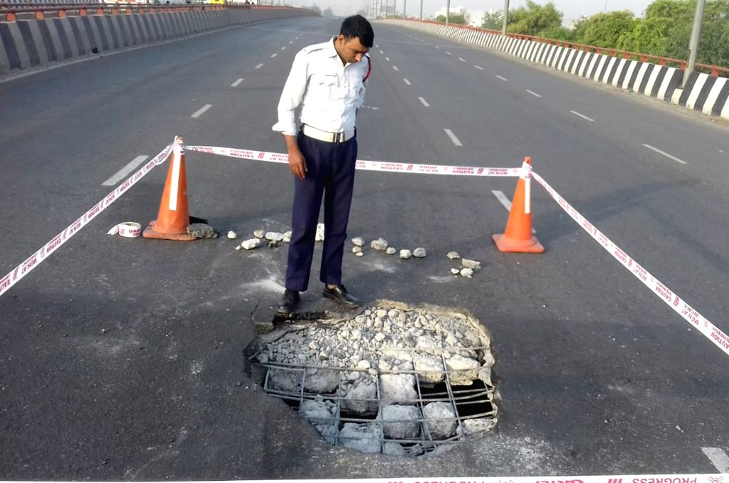 A traffic police officer inspects a large four feet hole which appears on the Hero Honda Chowk flyover on the Delhi-Jaipur stretch of the National Highway 8, in Gurugram, on May 8, 2019.