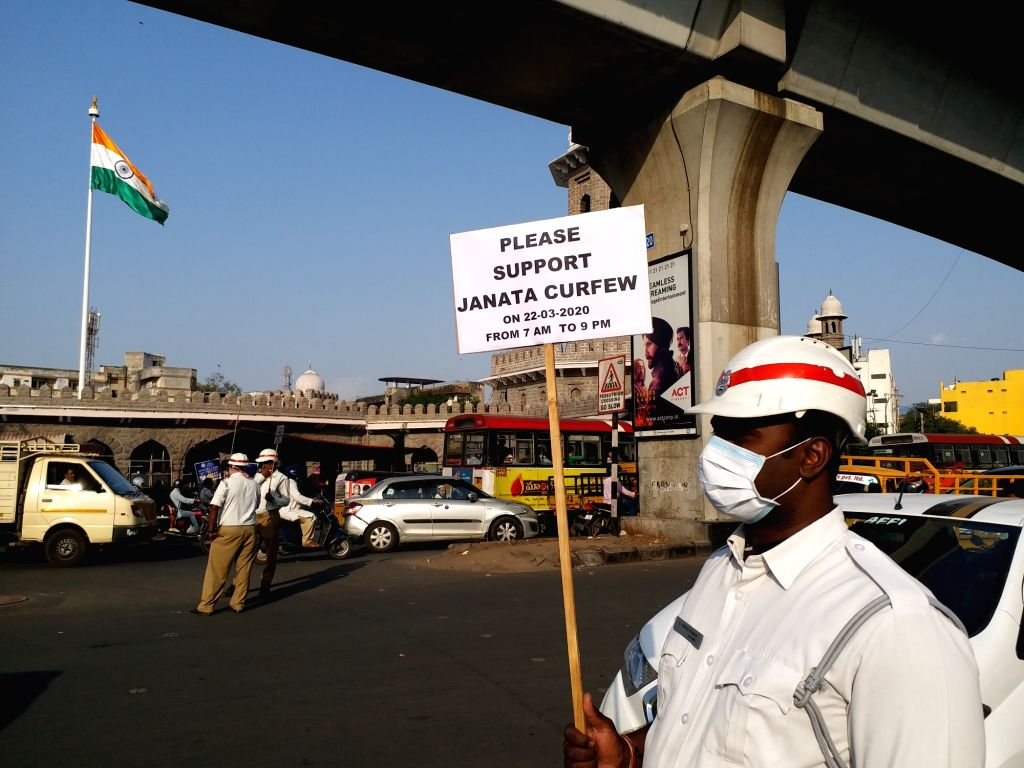 """A traffic police personnel displays a placard that reads """"Please Support Janata Curfew"""" ahead of Sunday's nationwide 'Janata Curfew' imposed in the wake of increasing cases of ..."""