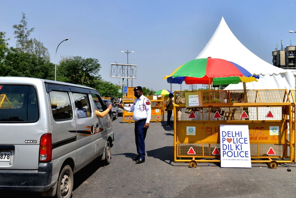 A traffic police personnel wearing a mask intercepts a commuter at the Delhi-Noida Border checkpoint during the extended nationwide lockdown imposed to mitigate the spread of coronavirus; ...