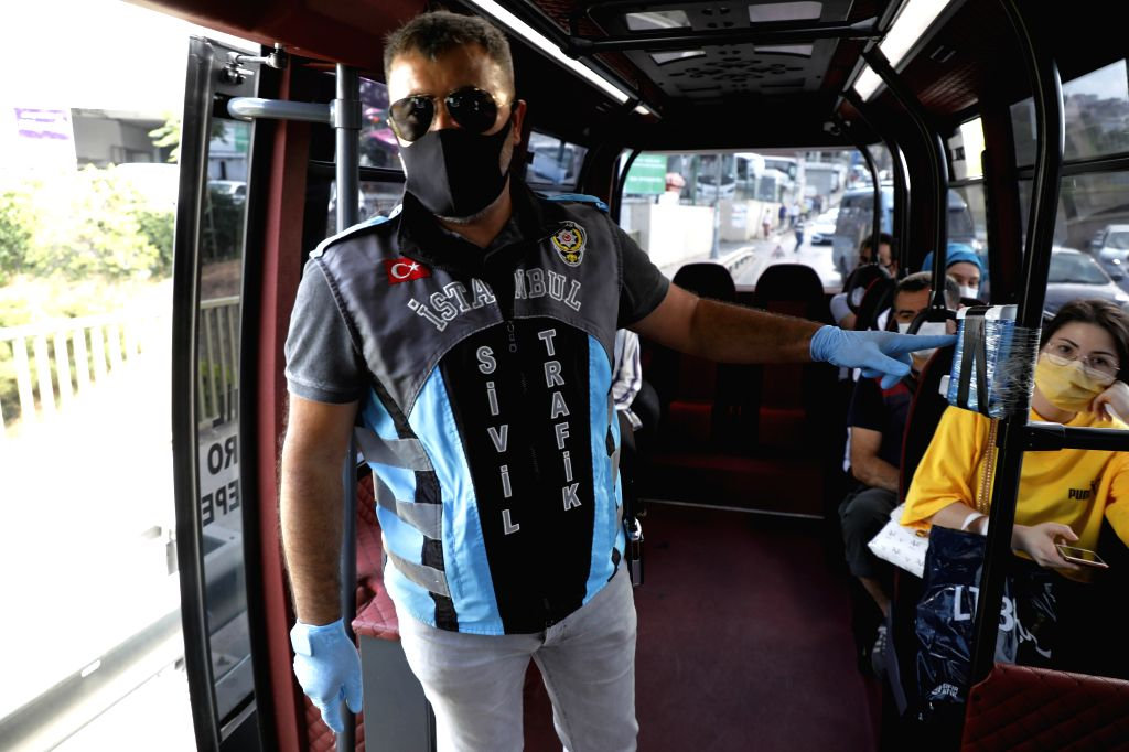 A traffic policeman checks a bus at a checkpoint in Istanbul, Turkey, on July 8, 2020. Turkey on Wednesday launched a nationwide inspection of the precautionary ...