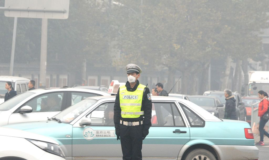 :A traffic policeman stands on a street in Jinan, capital of east China's Shandong Province, Nov. 12, 2015. Dense smog cloaked Jinan on Thursday.  (Xinhua/Feng ...