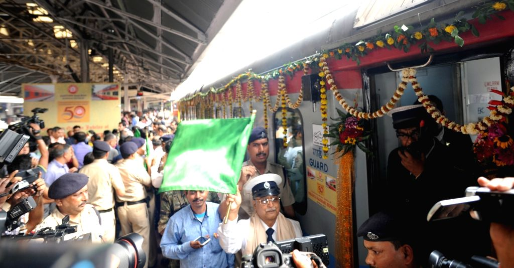 A Travelling Ticket Examiner (TTE) flags off during a programme organised to celebrate 50 years celebration of Howrah Rajdhani Express, in Howrah, on March 3, 2019.