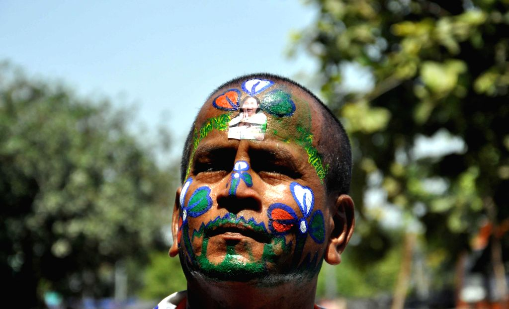 A Trinamool Congress (TMC) supporter with his face painted in party's colours in Kolkata on May 16, 2014.