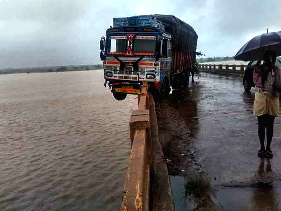 A truck dangling over the edge of a bridge after a crash in Medak district of Telangana on Sept 24, 2016.