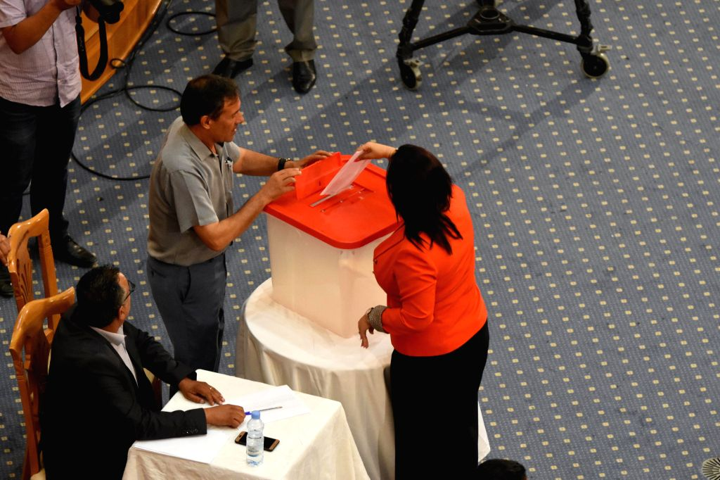 A Tunisian parliament member casts her vote in the parliament in Tunis, Tunisia, on July 30, 2020. Tunisian Parliament Speaker Rached Ghannouchi has retained his ... - Rached Ghannouchi