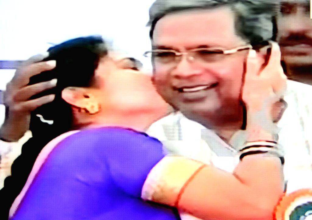 A TV grab of newly-elected Karnataka local body member Girija Srinivas planting a kiss on Karnataka CM Siddaramaiah's cheek at a felicitation programme in Bengaluru on Sunday ? photo by IANS.