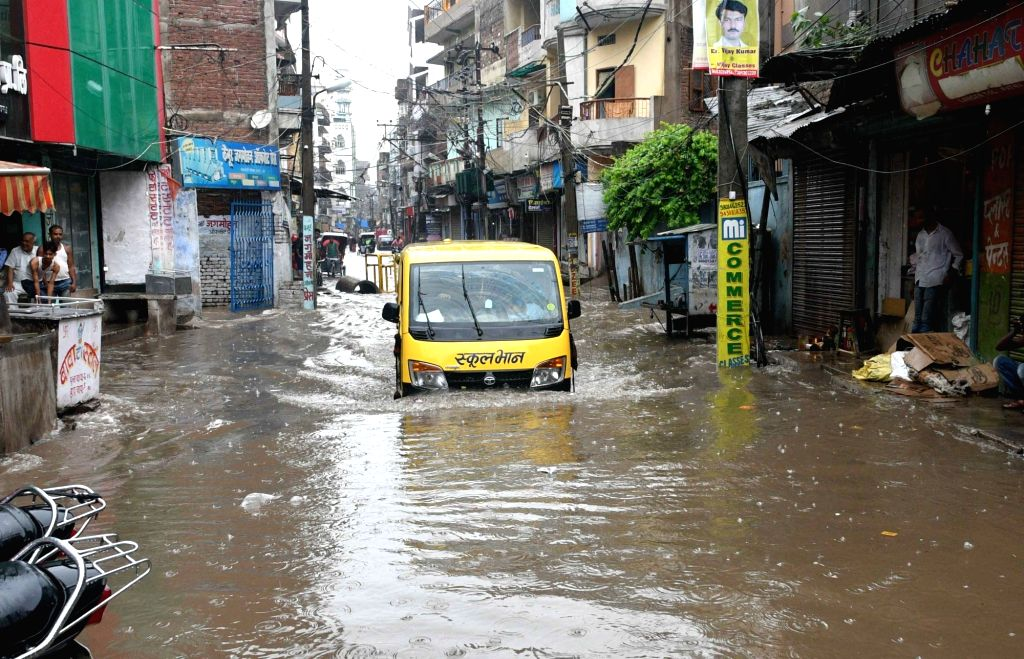 A van struggles through a water-logged street after heavy rains, in Patna on July 26, 2018.