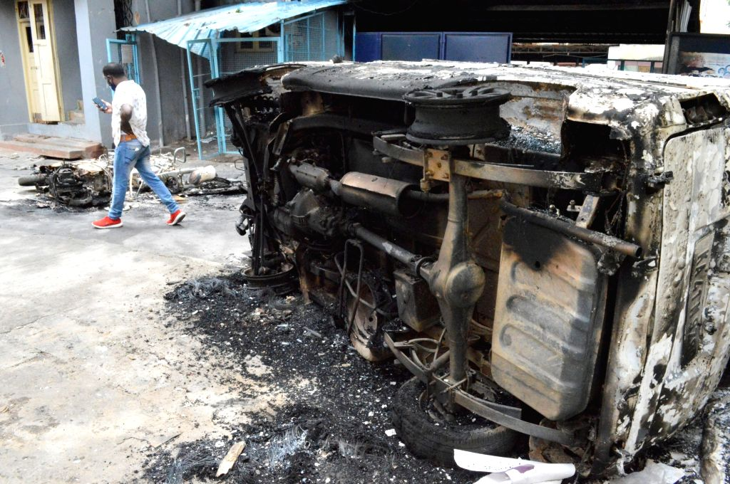 A vehicle burnt by an irate mob during violence  that erupted late on Tuesday night that resulted after an inflammatory social media post by Congress legislator Akanda Srinivas Murthy's ...