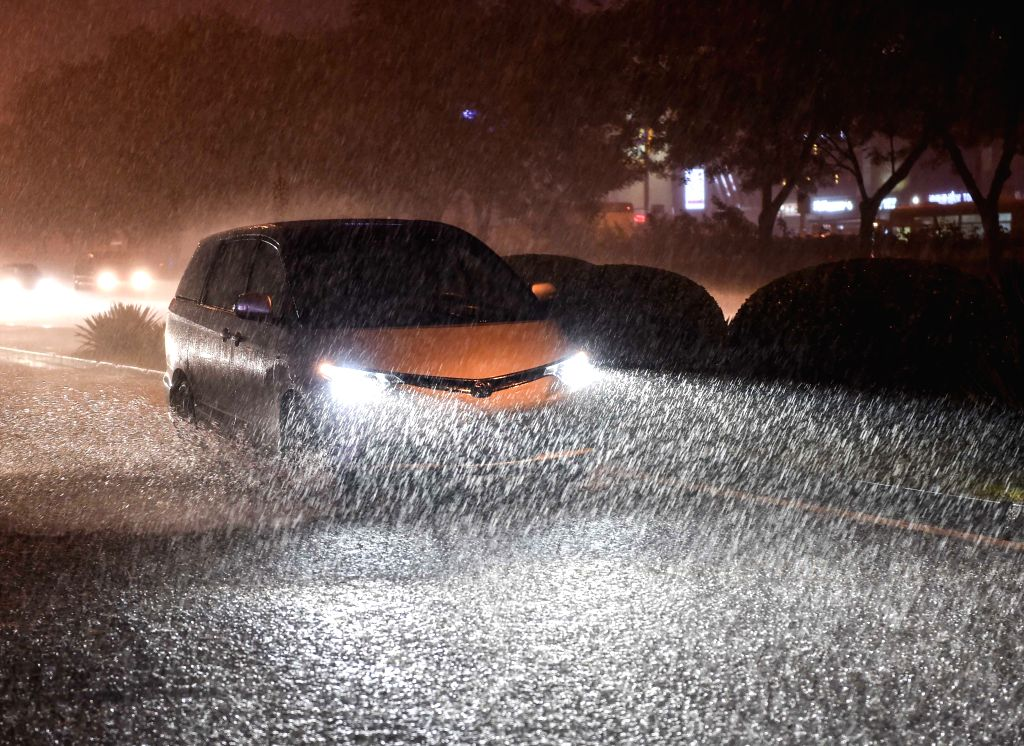 A vehicle moves at a rainy night in Beijing, China, July 27, 2015. As heavy rain hit Beijing on Monday, local weather station issued a yellow signal warning for ...