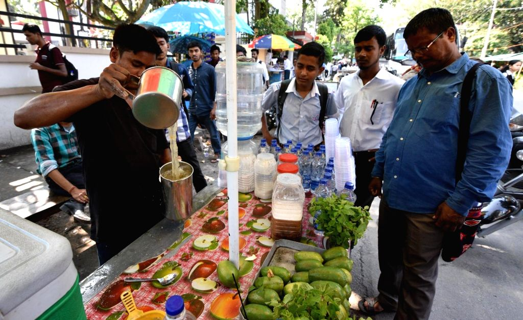 A vendor prepares lemonade as people wait to quench their thirst on a hot sunny day, in Guwahati on May 21, 2018.
