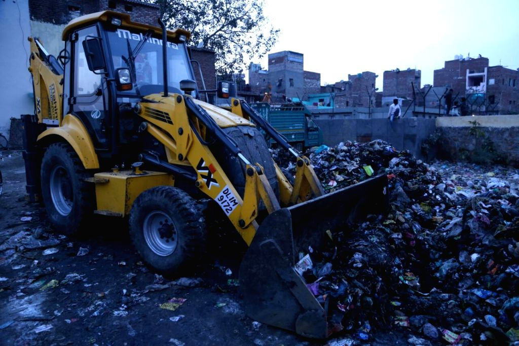A view of a loader, which was lifting the garbage nearby, suddenly hit the wall of the dump leading to its collapse killing a 30-year-old rag-picker Marjina while her husband Ansar Ali and ...