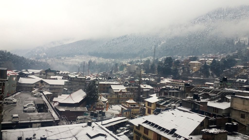 A view of Manali after fresh snowfall covers roof of houses and the tree-covered mountains on Feb 12, 2018.