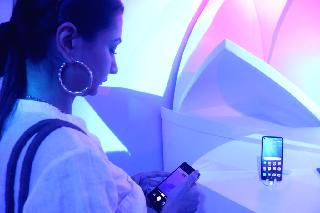 A visitor checks out the features of the newly launched Honor 20 Pro smartphone at the launch of Honor 20 Pro, 20 and 20i smartphones, in New Delhi on June 11, 2019.