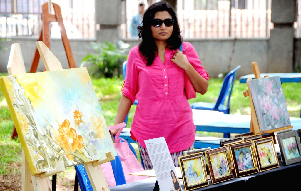 A visitor during spot painting exhibition at Art Park Bangalore Ravindra Kalakshetra in Bangalore on Sept 7, 2014.