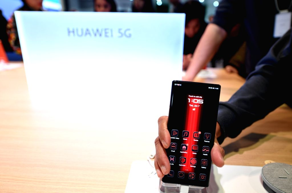 A visitor experiences a 5G smart phone at the booth of Huawei at the 2020 Consumer Electronics Show in Las Vegas, the United States, Jan. 7, 2020. The annual tech ...