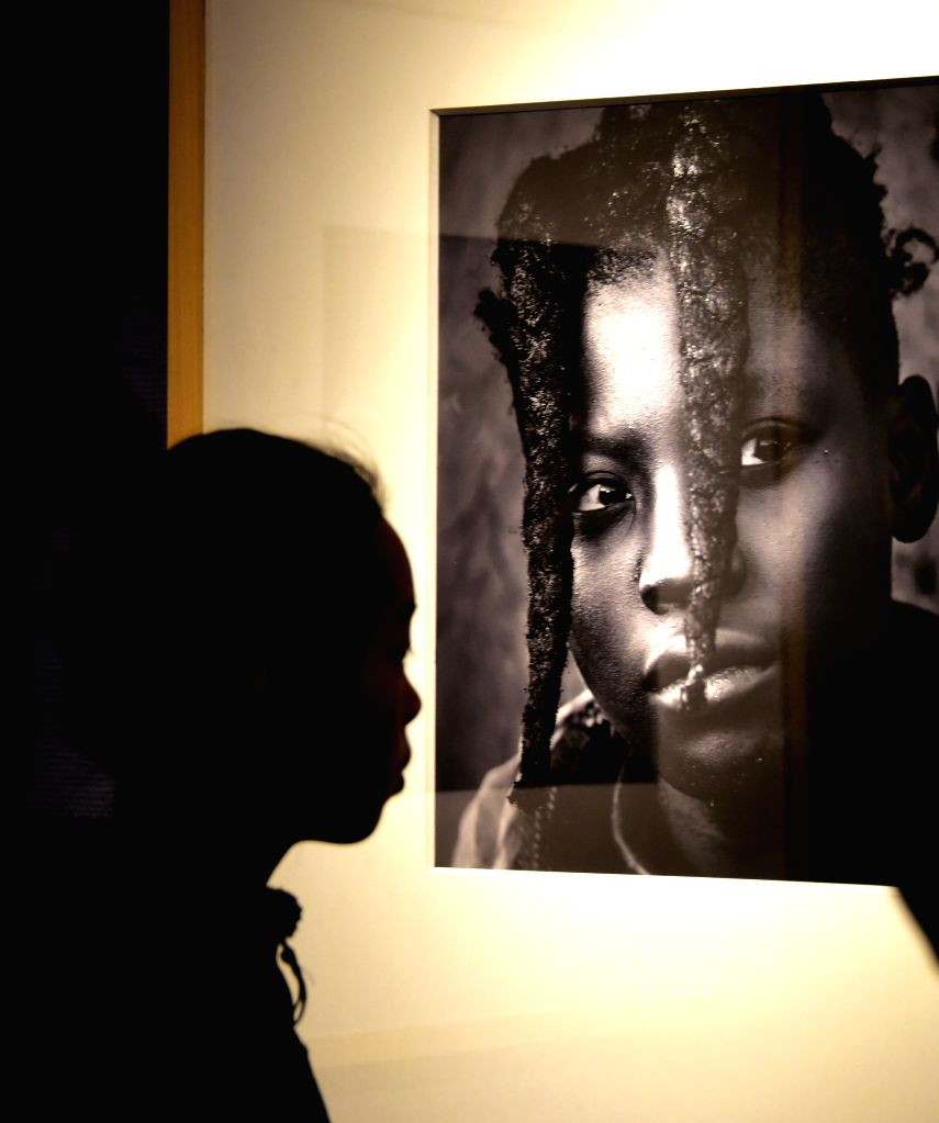 A visitor looks at a picture during a photo exhibition about Africa, at the Hubei Museum in Wuhan, capital of central China's Hubei Province, Jan. 17, 2016. The ...