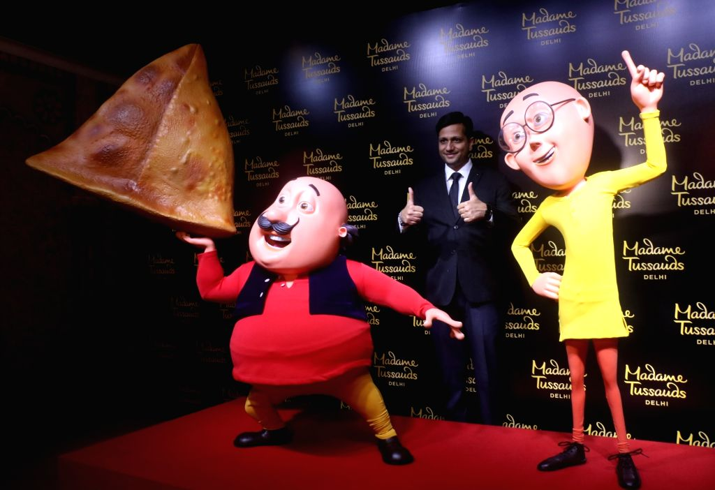 A visitor poses with the newly launched wax statues of cartoon characters 'Motu' and 'Patlu' at Madame Tussauds museum in New Delhi on June 4, 2019.