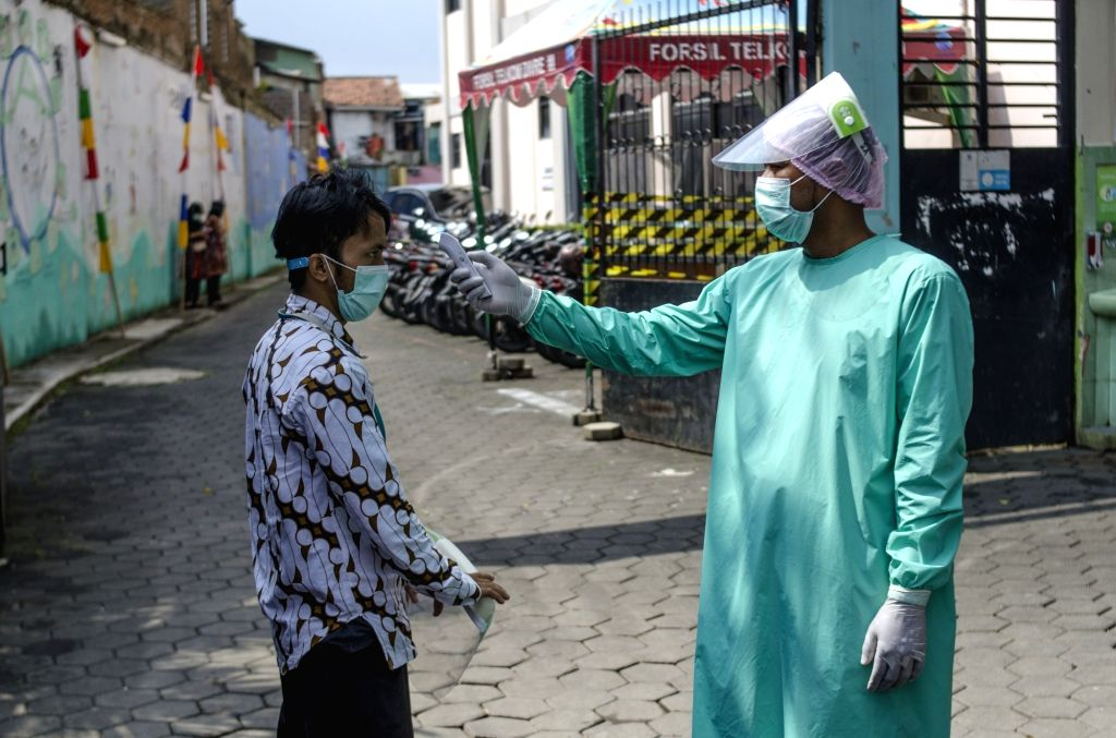 A volunteer gets body temperature check by a health officer before participating in a vaccine clinical trial at Garuda clinic in Bandung, West Java, Indonesia, Aug. ...