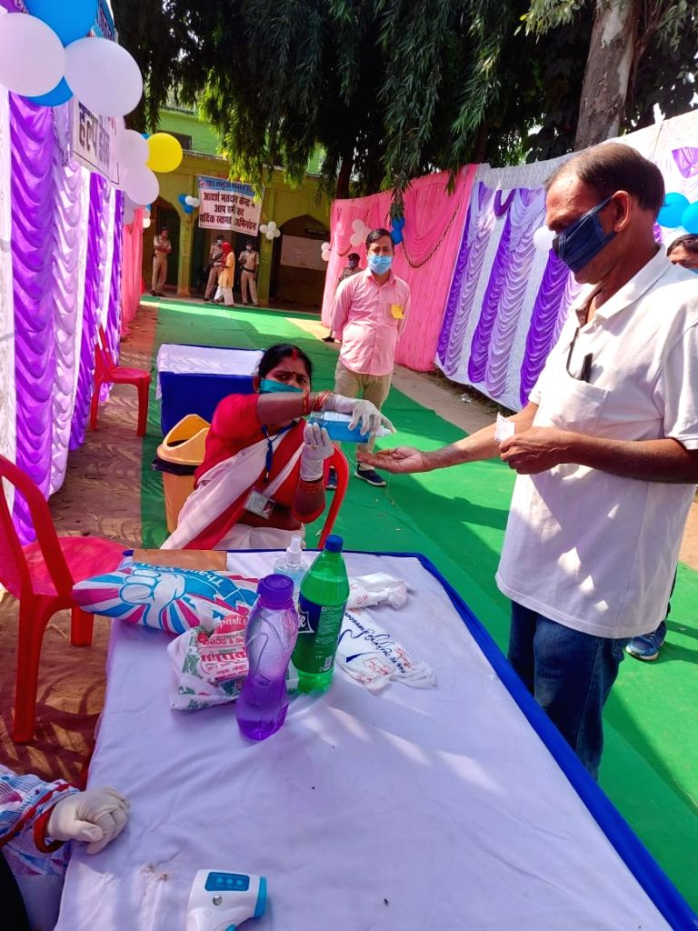 A voter being provided with hand sanitiser as he arrives to cast his vote for the first phase of Bihar Assembly elections, at a polling station in Kaimur district on Oct 28, 2020.