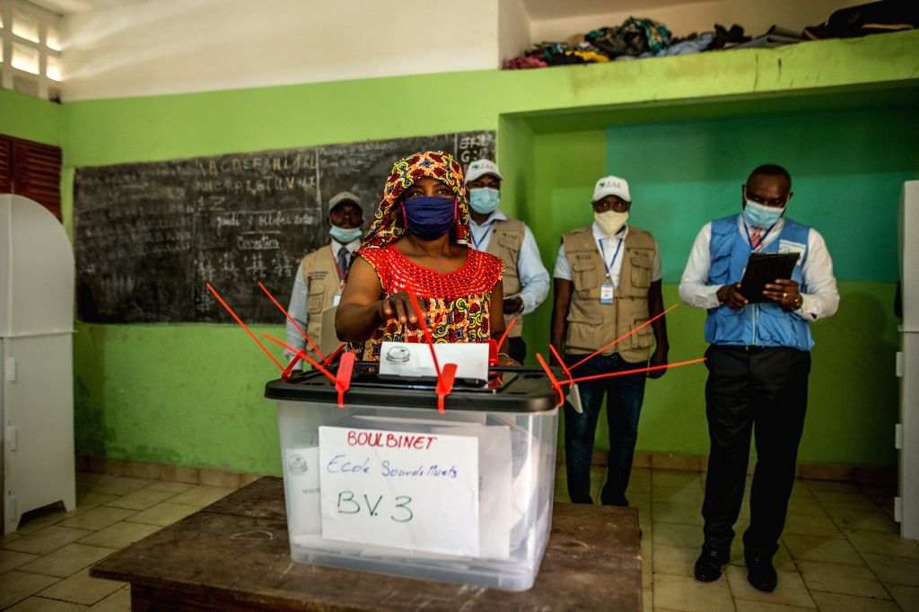 A voter casts his ballot at a polling station in Conakry, Guinea, Oct. 18, 2020. Guinean citizens began to vote in the presidential election on Sunday morning. A ...