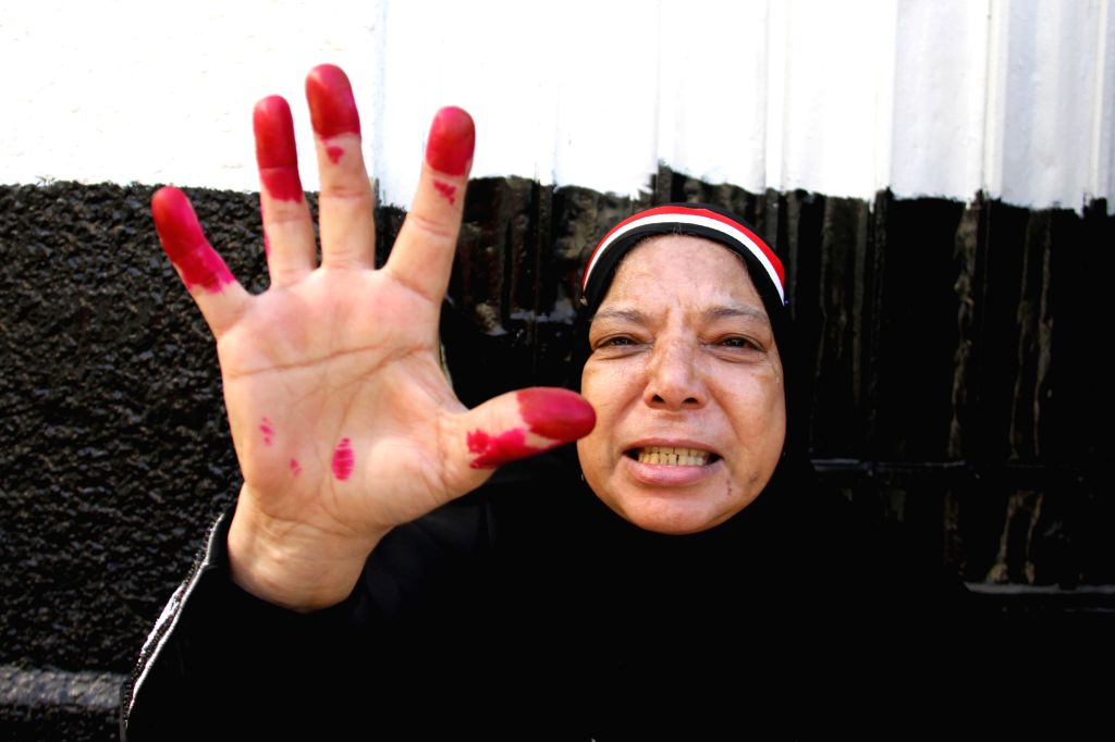 A voter displays her ink-strained fingers outside a polling station in Cairo, Egypt, on Nov. 22, 2015. Egyptians began voting Sunday in the second phase of the ...