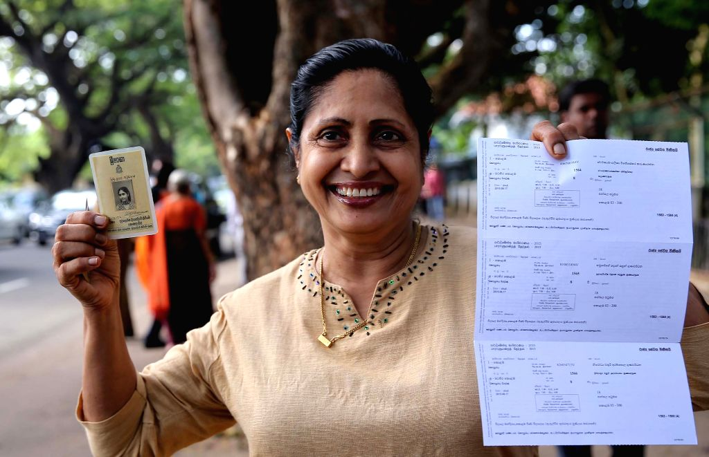 A voter shows her credentials at a polling center in Colombo, Sri Lanka, Aug. 17, 2015. Sri Lanka on Monday held elections for a new 225-member parliament. ...