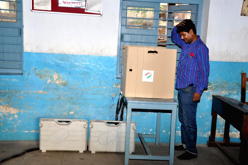 A voter taking a close look at the electronic voting machine before casting his vote during the fifth phase of Lok Sabha election in Ranchi, Jharkhand on April 17, 2014.