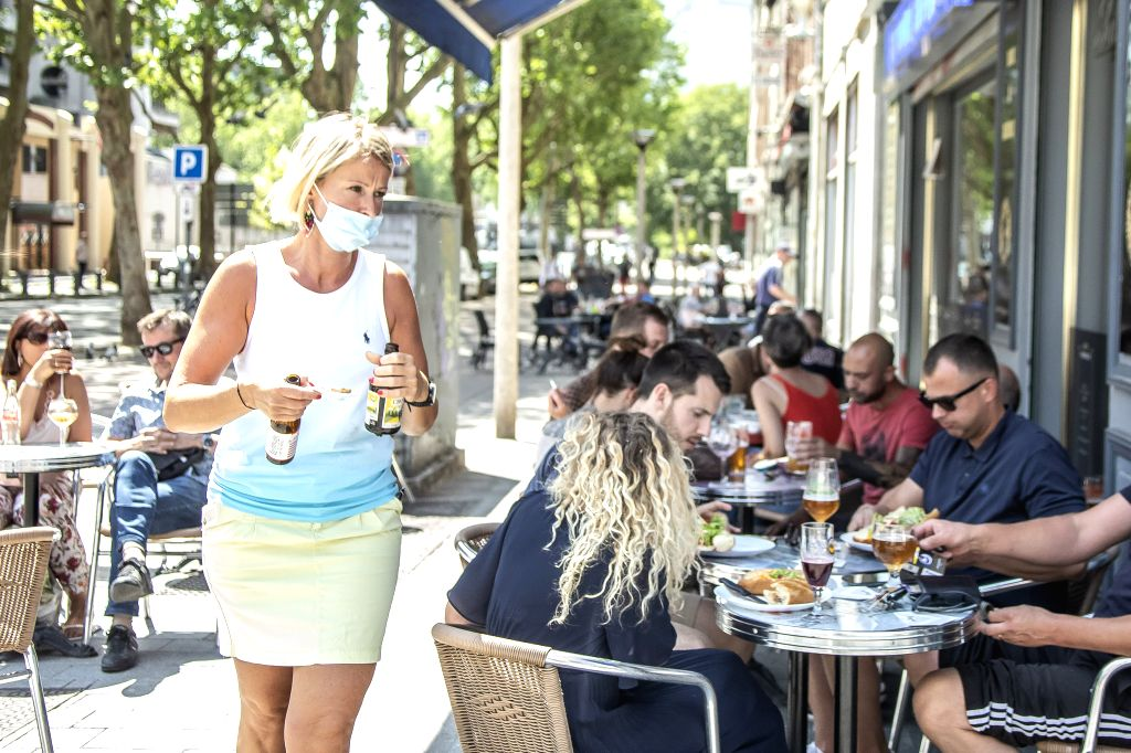 A waitress wearing a mask works at a restaurant in Lille, northern France
