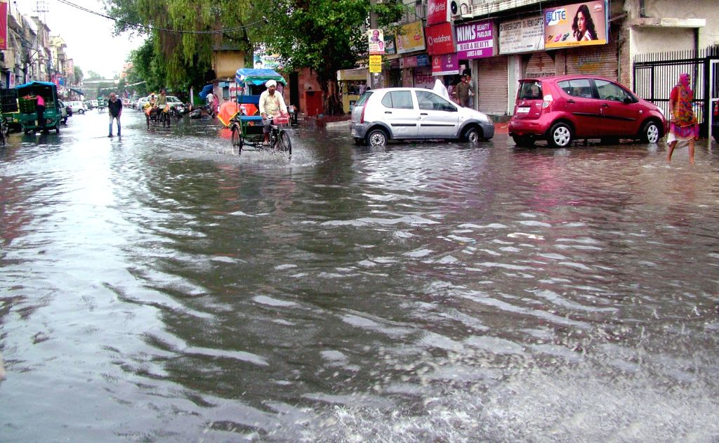 A water logged road in New Delhi after the rain on August 16, 2013. (Photo::: IANS)