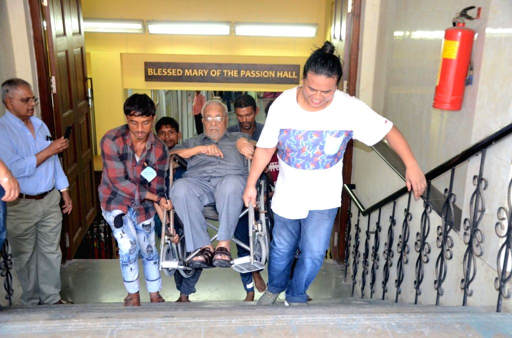 A wheel chair bound man being escorted to polling booth during the fourth phase of 2019 Lok Sabha elections, in Mumbai on April 29, 2019.