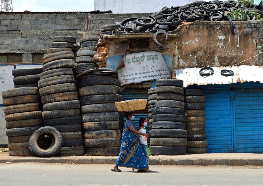 A woman and a girl walk past a deserted street at Kalasipalya area during a strict lockdown that has been re-imposed for 15 days in five wards across Bengaluru to contain the spread of ...