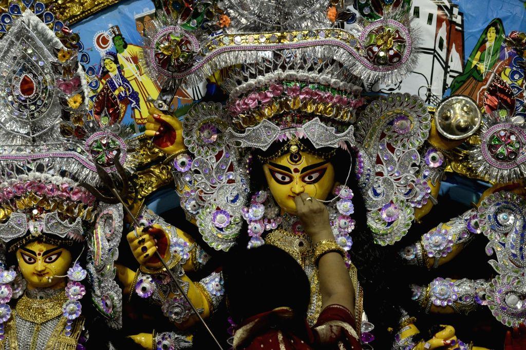 A woman applies vermilion to an idol of Goddess Durga during Vijayadashami celebrations, in Kolkata on Oct 8, 2019.
