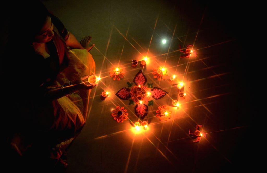 A woman arranges earthen lamps around a 'rangoli' during Diwali celebrations in Kolkata on Oct 26, 2019.
