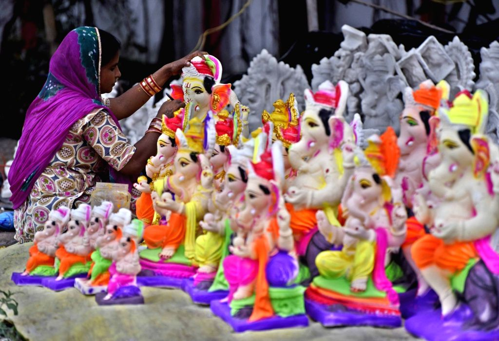 A woman artist gives finishing touches to an idol of Lord Ganesha ahead of Ganesh Chaturthi celebrations, in Patna on Aug 14, 2020.