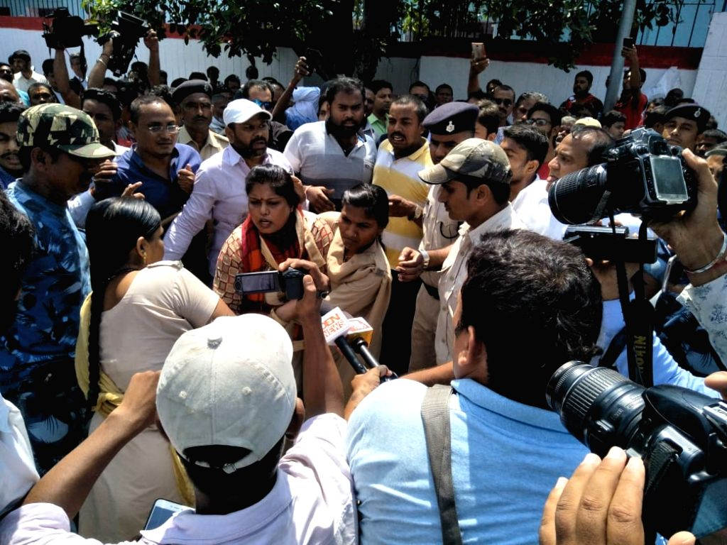 A woman being taken away by police personnel after a group of women blackened the face of Brajesh Thakur, the main accused in the Bihar shelter home horror case, while he was coming out ...