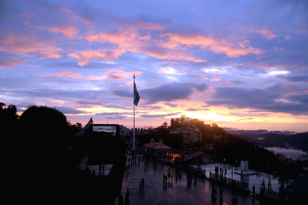 A woman captures the bright skies with an orange tinge left behind by the sun during sunset after rains, in Shimla on Aug 8, 2018.